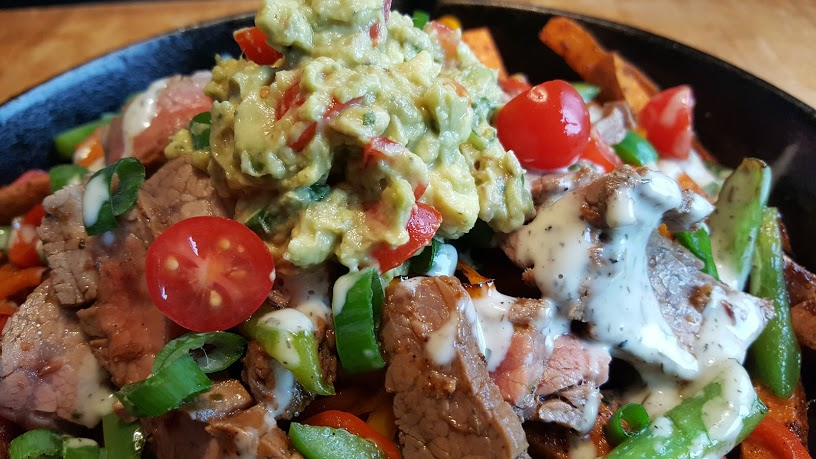 Whole30 Loaded Sweet Potato Fries topped with guacamole green onion and tomatoes.