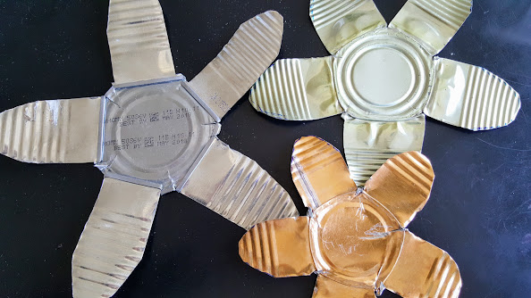 Tin cans were snipped and cut to make a painted metal flower