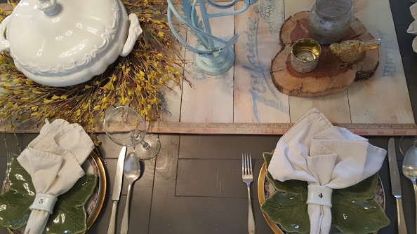 Elegant and simple table setting with wooden farmhouse table runner and forsythia wreath