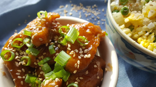 Whole30 orange chicken sprinkled with sesame seeds and green onions