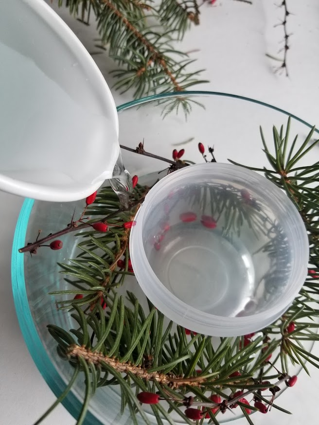 filling decorative ice bowl with branches and berries